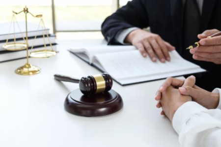 Close up of gavel, Male lawyer or judge Consult with client and working with Law books, report the case on table in modern office, Law and justice concept